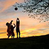 Children play ball at sunset